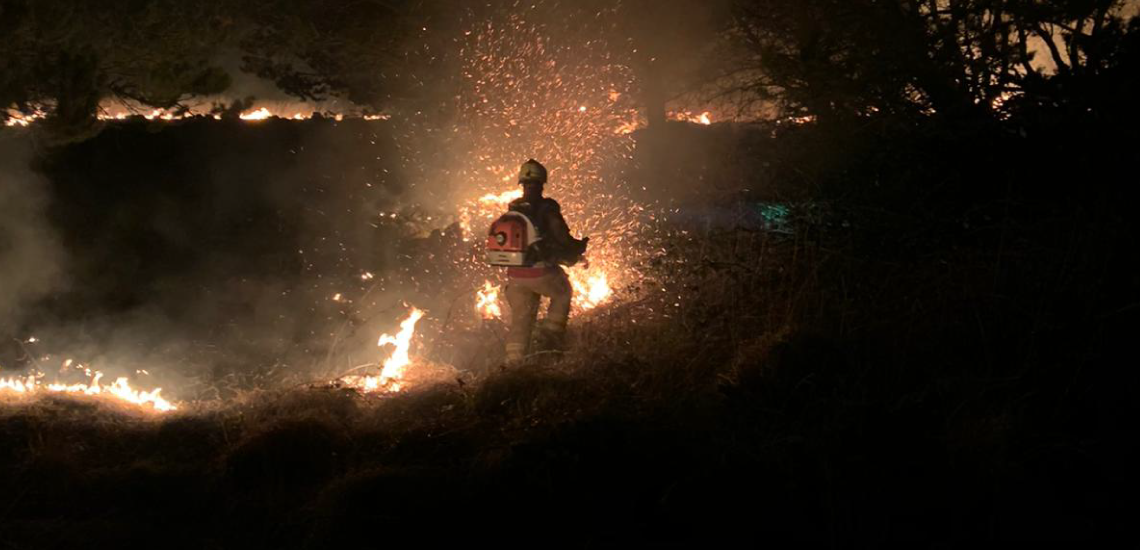 Lone firefighter fighting a wiildfire.