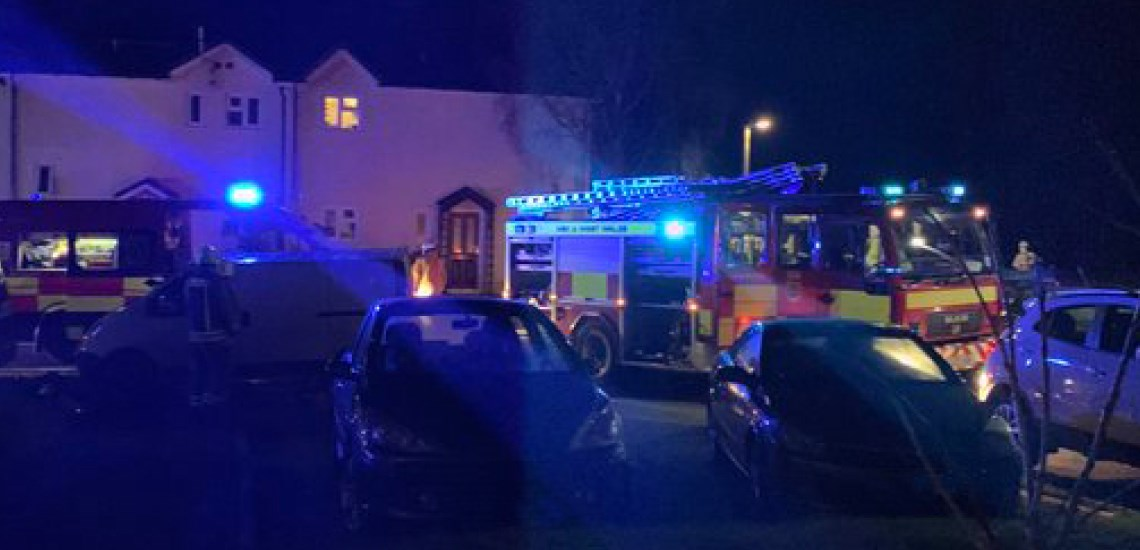 Incident photograph, fire appliances outside a property at night